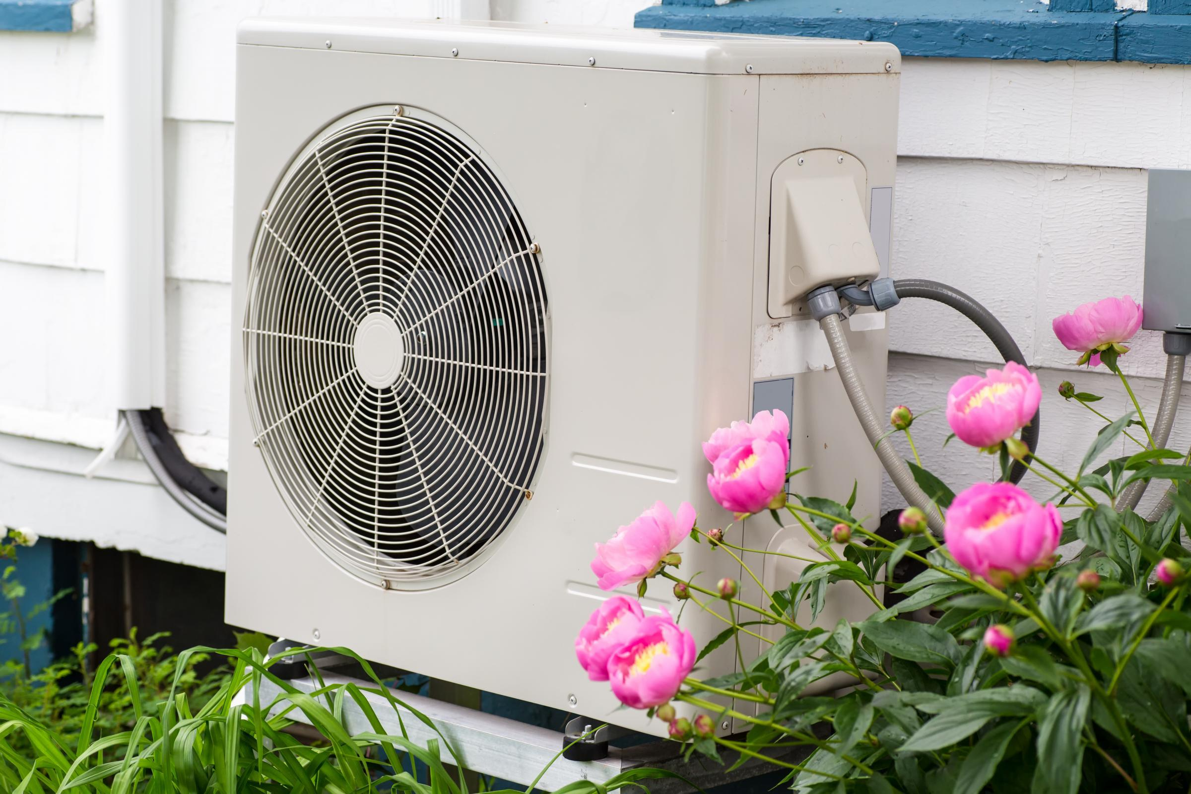 electric heat pump on exterior of house next to flowers