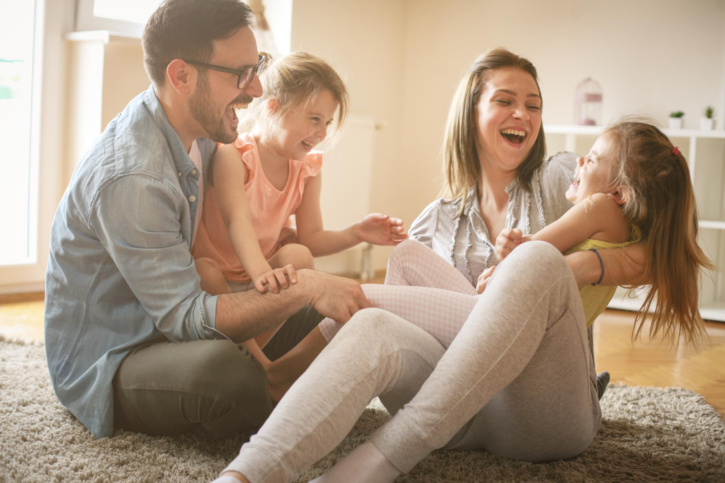 Happy Family Laughing and Playing on Living Room Floor